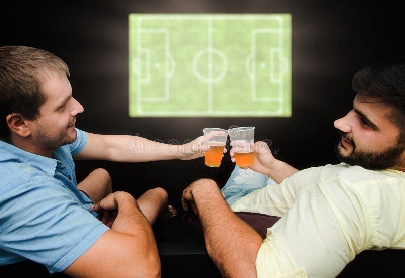 Los fans masculinos miran fútbol en la TV y beben la cerveza Los amigos tienen una cerveza de consumición del gran tiempo imagen de archivo libre de regalías