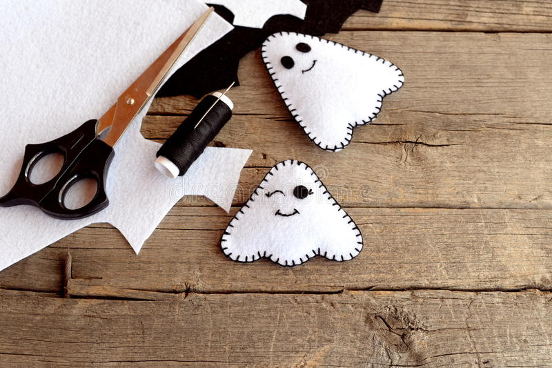 Los fantasmas blancos divertidos diy, fieltro de Halloween cubren, las tijeras, hilo, agujas en un viejo fondo de madera Hallowee foto de archivo