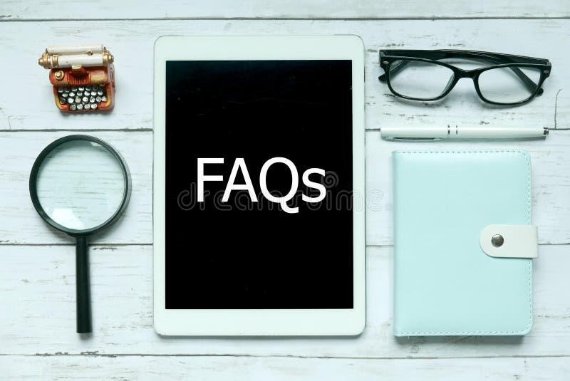 Los FAQ digitales en línea pidieron con frecuencia concepto de las preguntas Vista superior de la lupa, del cuaderno, de la pluma fotografía de archivo libre de regalías