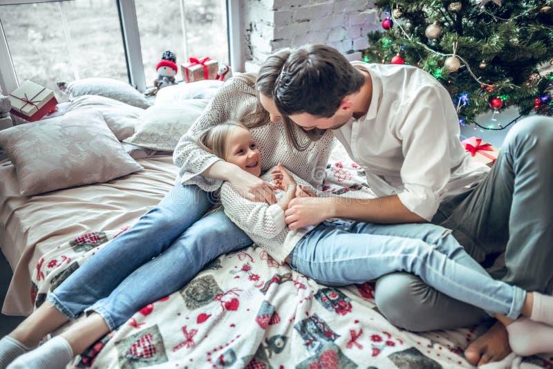 Los felices padres y niño de la muchacha juntos hacen los planes por días de fiesta de la Navidad fotografía de archivo