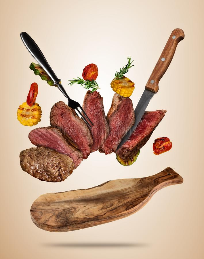 Los filetes de carne de vaca del vuelo con la verdura asada a la parrilla sirvieron en cutti de madera stock de ilustración