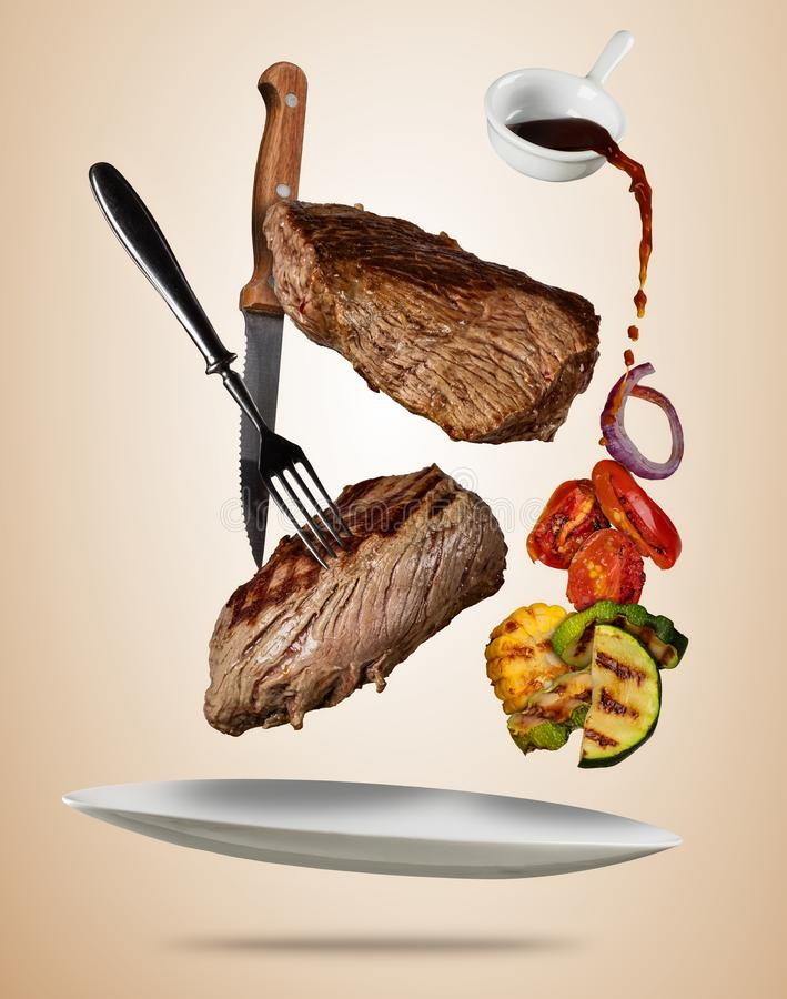Los filetes de carne de vaca del vuelo con la verdura asada a la parrilla sirvieron en la placa stock de ilustración