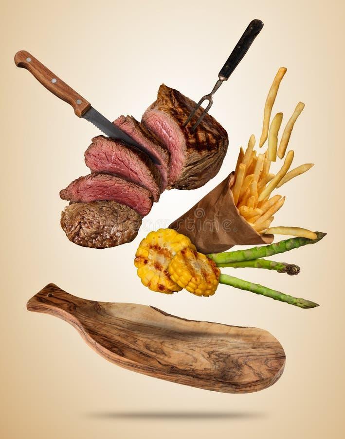 Los filetes de carne de vaca del vuelo con la verdura y las patatas fritas asadas a la parrilla sirven libre illustration