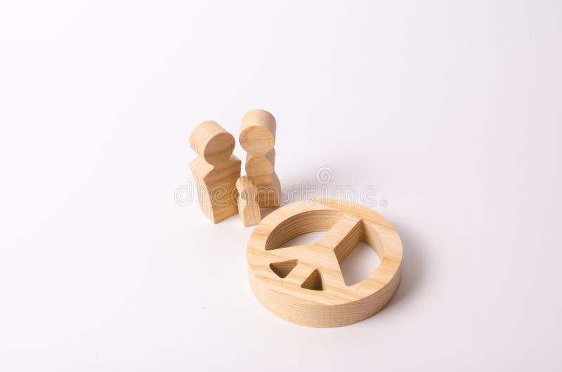 Los finales de madera del ` s de la gente se colocan cerca de la muestra de la paz, del desarme y del movimiento pacífico El conc fotografía de archivo libre de regalías