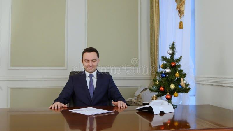 Los finales del hombre de negocios trabajan con éxito con los documentos y se van por días de fiesta de una Navidad fotografía de archivo