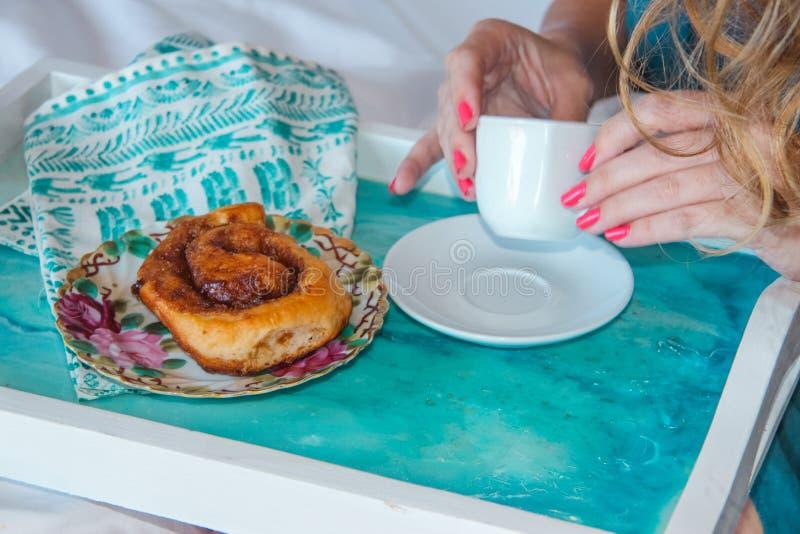 Los fingeres de la hembra que sostienen una taza de café con un panecillo en una placa en una bandeja del mármol del azul de ciel imagenes de archivo