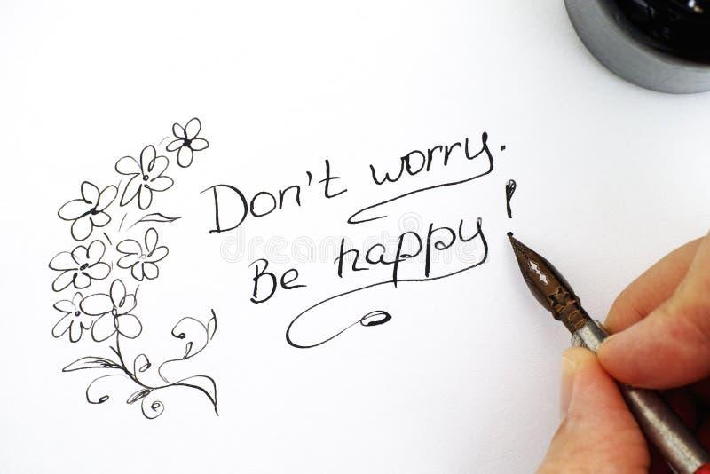 Los fingeres de la mujer con frase de la escritura de la pluma no se preocupan ¡Sea feliz! fotografía de archivo