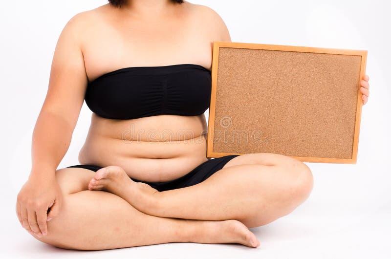 Los fingeres de la mujer que miden su grasa del vientre fotografía de archivo