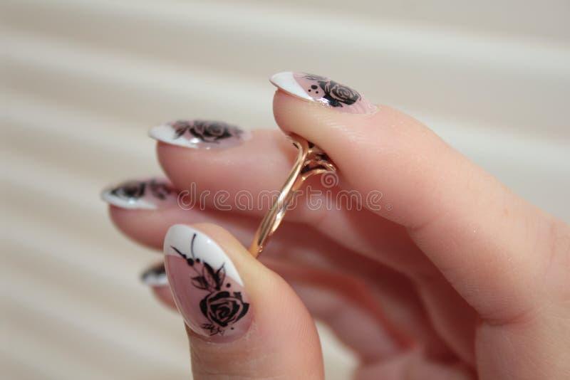 Los fingeres femeninos llevan a cabo el anillo Manicura francesa imágenes de archivo libres de regalías
