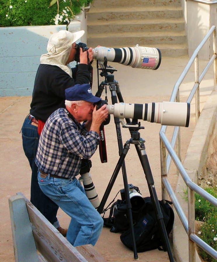 Los fotógrafos profesionales toman las fotos con las cámaras grandes foto de archivo libre de regalías