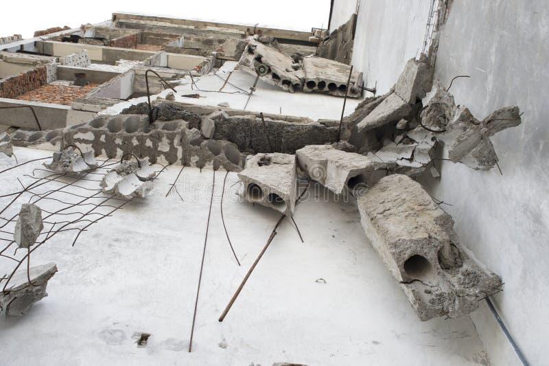 Los fragmentos concretos cuelgan en el refuerzo en la pared del edificio destruido Fondo Visi?n inferior fotografía de archivo libre de regalías