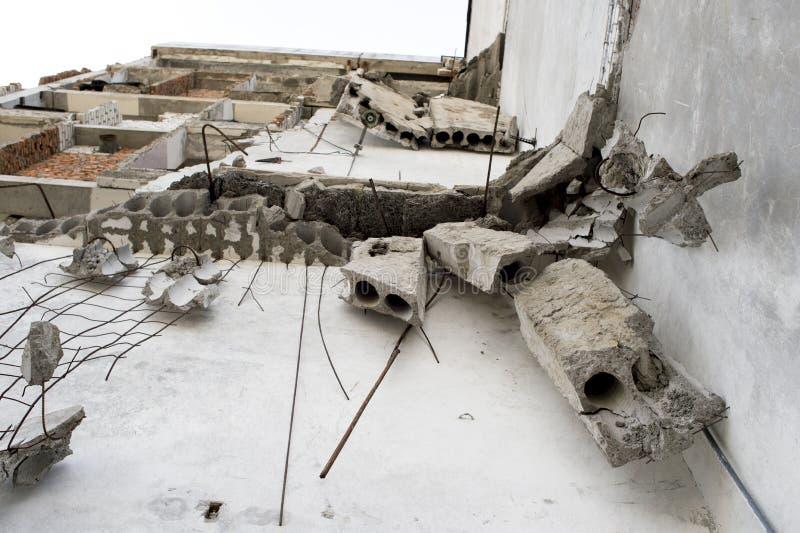 Los fragmentos concretos cuelgan en el refuerzo en la pared del edificio destruido Fondo Visi?n inferior fotos de archivo libres de regalías