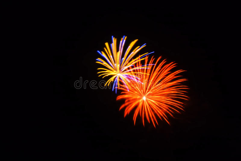 Los fuegos artificiales anaranjados, amarillos, azules y rosados brillan brillante en el cielo imágenes de archivo libres de regalías