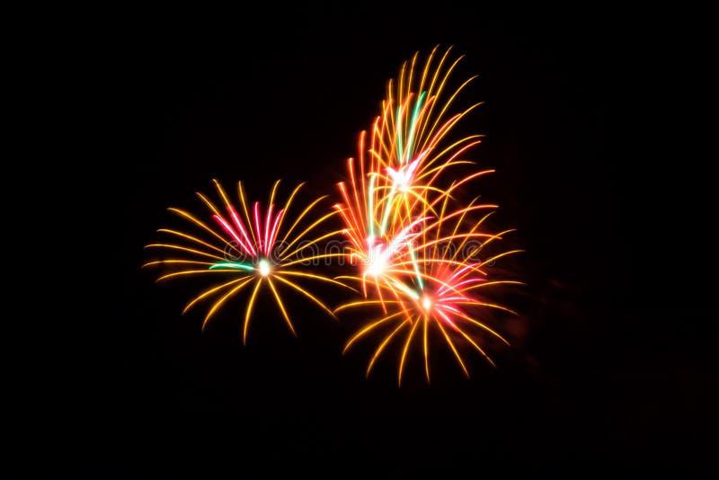 Los fuegos artificiales anaranjados y rosados encienden el cielo imagen de archivo libre de regalías