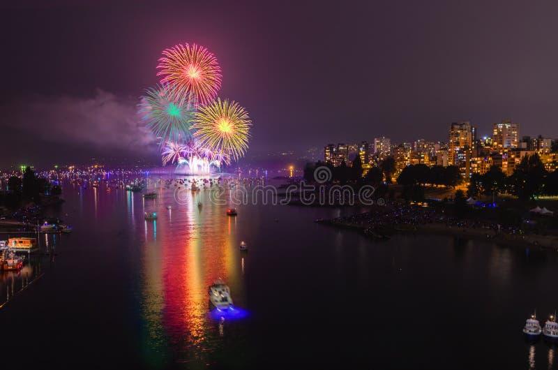 Los fuegos artificiales multicolores se encienden sobre el océano cerca de la ciudad grande imagen de archivo libre de regalías