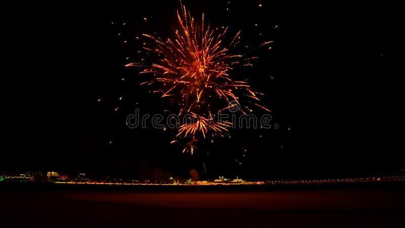 Los fuegos artificiales rojos explotan tarde en la noche en la calle imagen de archivo