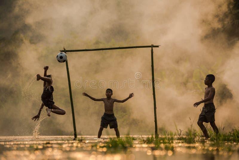 Los futbolistas los tres niños están jugando a fútbol en fotos de archivo libres de regalías
