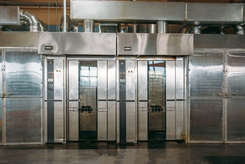 Los gabinete-hornos o las estufas industriales para la preparación de galletas y de la panadería en la fábrica de la confitería,  imagen de archivo libre de regalías