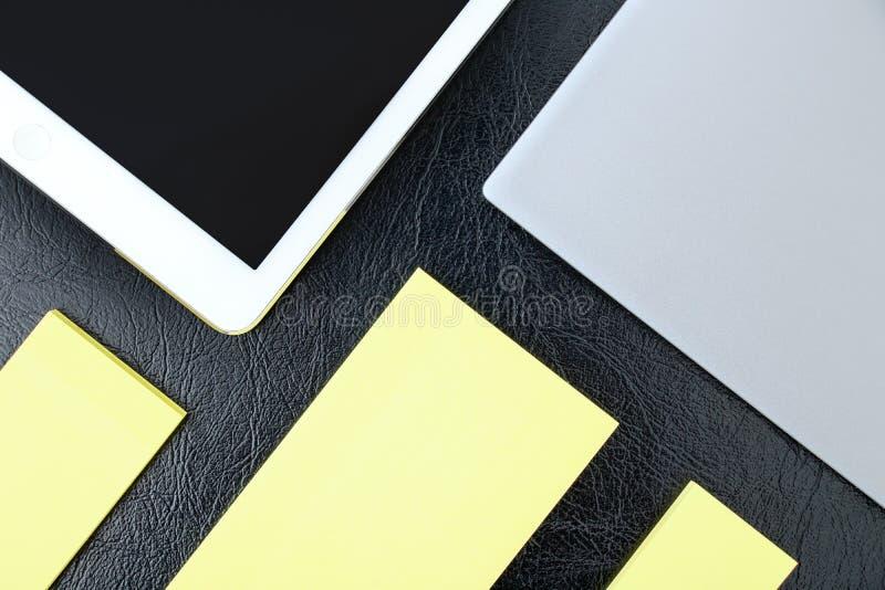 Los gastos indirectos de la tabla de la oficina con el cuaderno, PC de la tableta y amarillean no imagenes de archivo