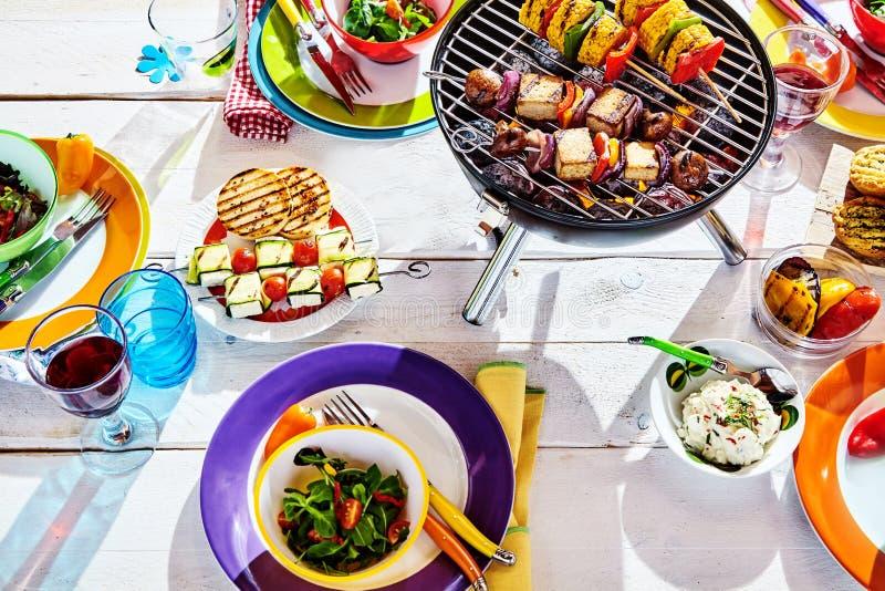 Los gastos indirectos pusieron bien la tabla del verano con el plato y el brasero coloridos foto de archivo libre de regalías