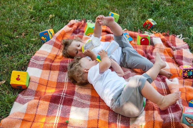 Los gemelos de los niños ponen en la sobrecama entre los juguetes foto de archivo