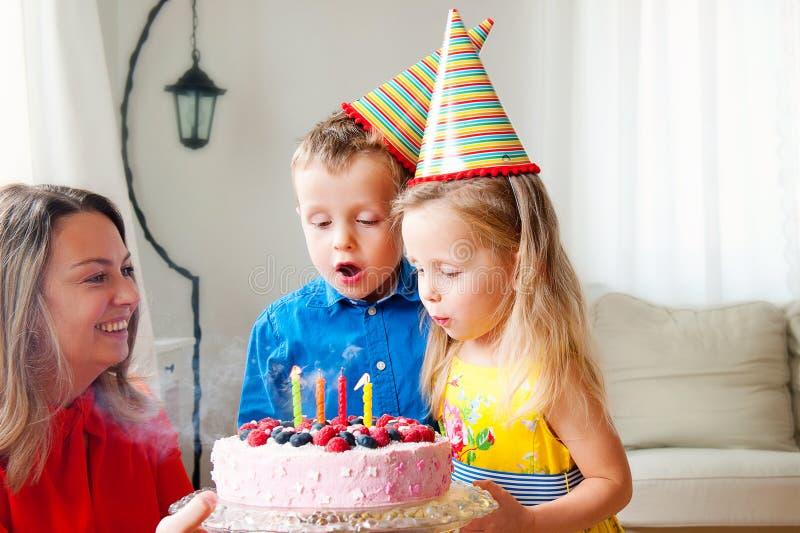 Los gemelos preciosos de la muchacha y del muchacho en sombreros del partido soplan hacia fuera cuatro velas en una torta de cump imágenes de archivo libres de regalías