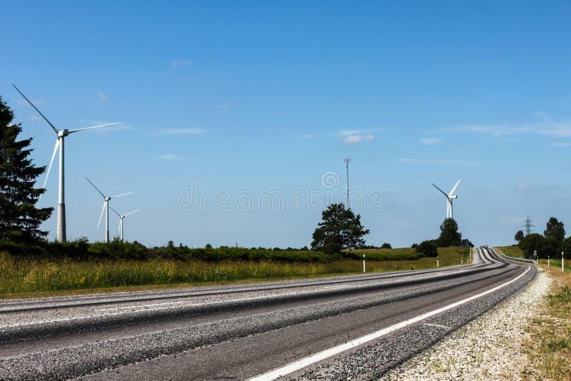 Los generadores de viento acercan al camino foto de archivo