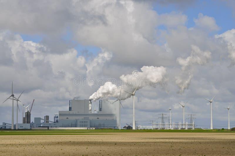Los generadores eólicos alinean una central eléctrica grande del combustible fósil imagen de archivo libre de regalías