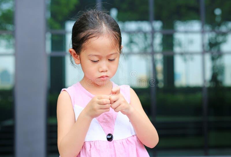 Los gestos de los ni?os que carecen confianza La muchacha del niño piensa sus fingeres fotografía de archivo libre de regalías