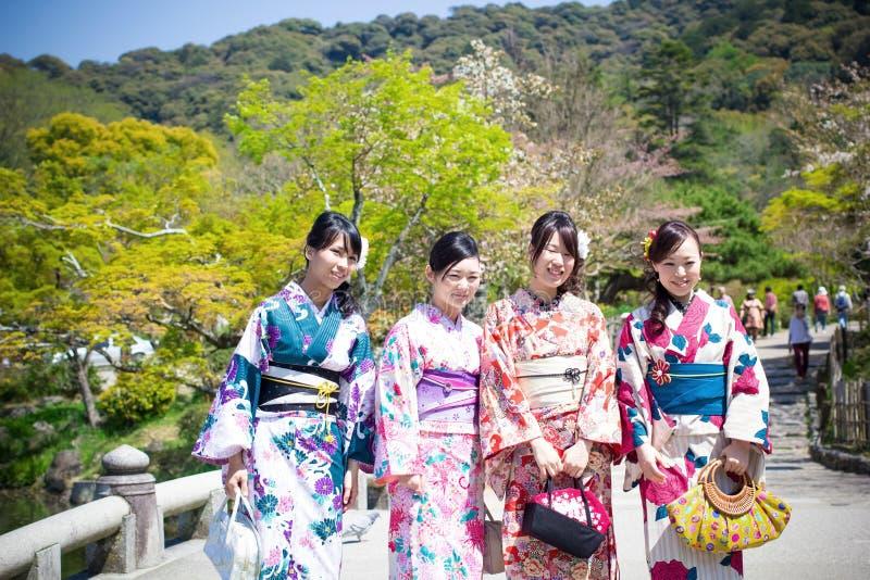 Los gilrs de Apanese con el traje tradicional japonés (Yukata) están caminando en la capilla próxima localizada parque de Maruyam foto de archivo