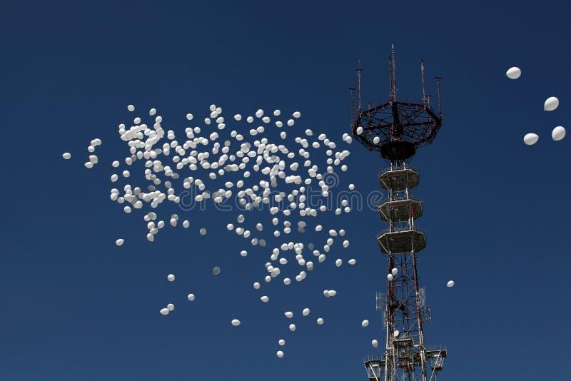Los globos blancos vuelan contra la perspectiva de una torre de la televisión en la ciudad de Minsk, Bielorrusia foto de archivo libre de regalías