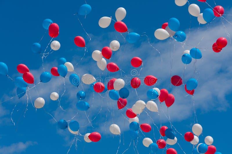 Los globos coloreados vuelan en el cielo imagenes de archivo