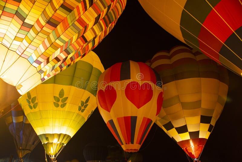 Los globos del aire caliente brillan intensamente en el flotador de la noche en festival imagen de archivo