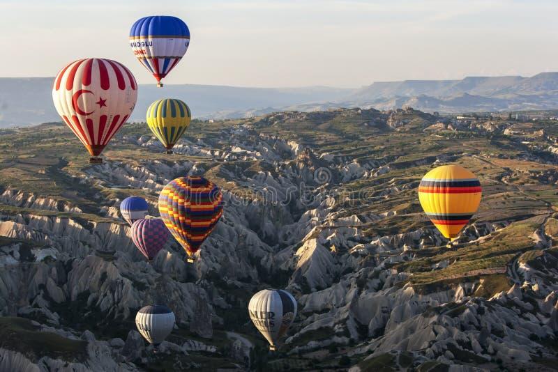 Los globos del aire caliente vuelan sobre el paisaje hermoso cerca de Goreme en la región de Cappadocia de Turquía imagen de archivo