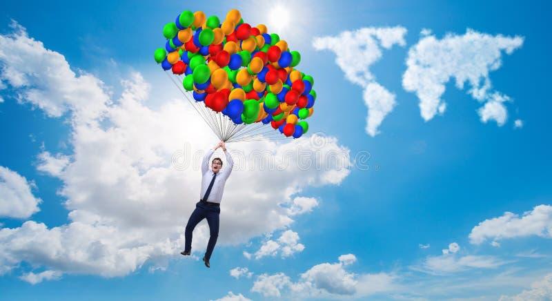 Los globos del vuelo del hombre de negocios en día brillante imagenes de archivo