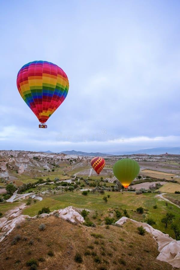 Los globos grandes vuelan sobre las montañas en Cappadocia fotos de archivo