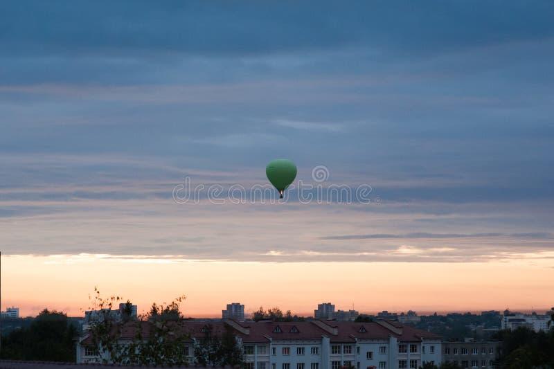 Los globos vuelan para arriba en cielo con los pasajeros sobre campo verde Aerostato en aire Globo verde en el cielo imágenes de archivo libres de regalías