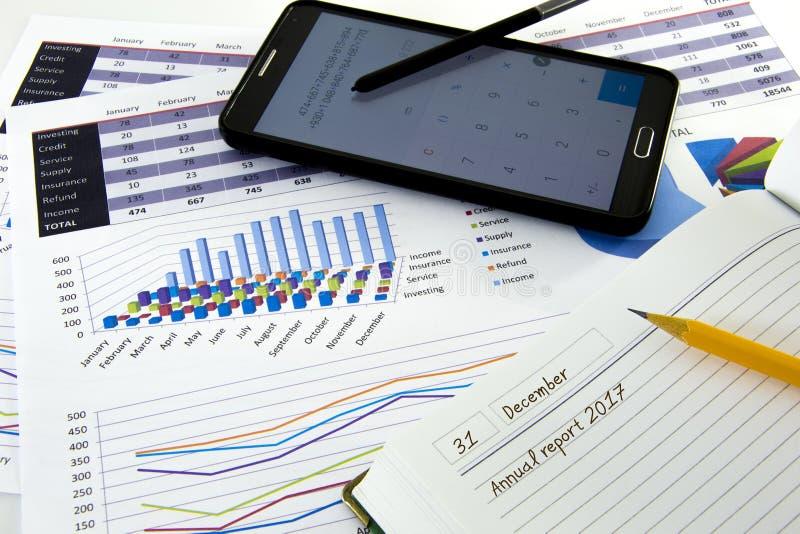 Los gráficos y las cartas de negocio divulgan con la pluma en el escritorio del consejero financiero Concepto financiero de la co fotografía de archivo libre de regalías