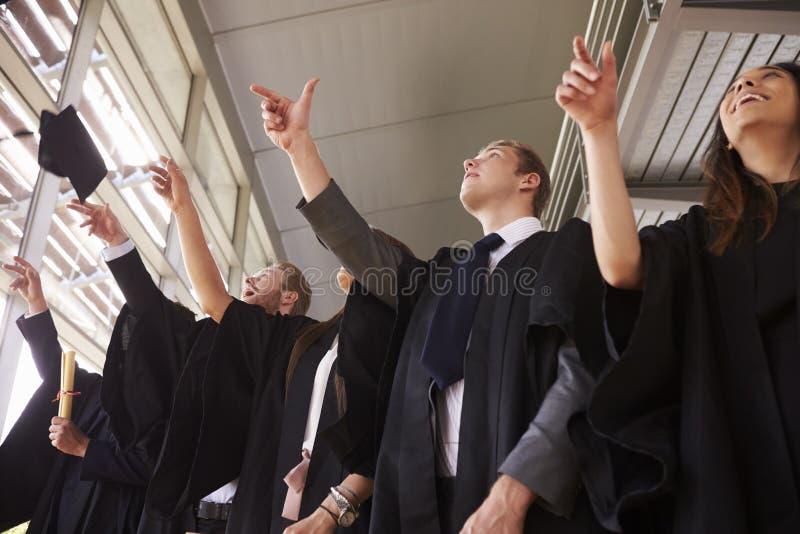Los graduados en los vestidos que lanzan su mortero suben en el aire imagen de archivo