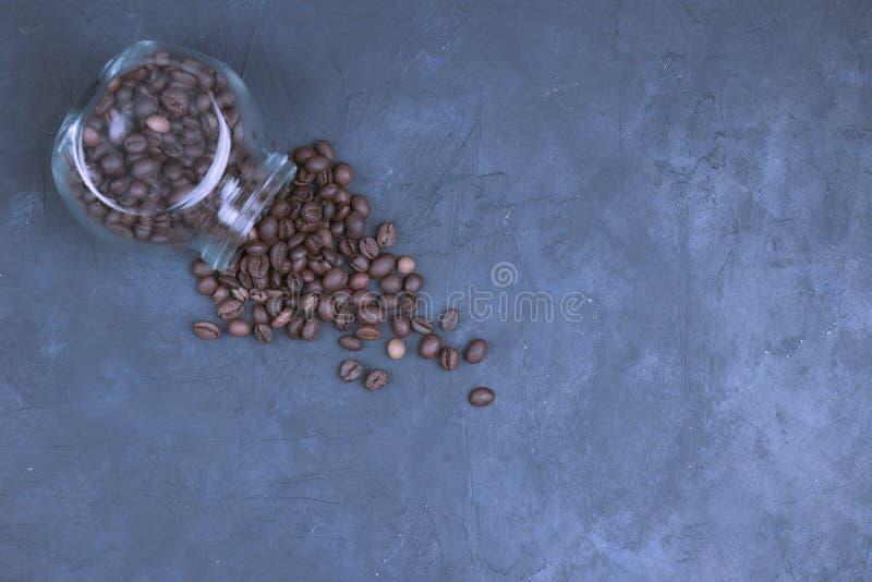Los granos de café asados vertieron de un tarro de cristal colocación angular del objeto del café en el hormigón oscuro Visión de foto de archivo libre de regalías