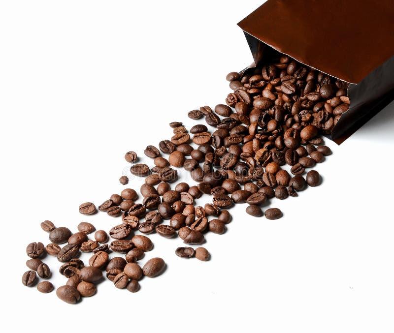 Los granos de café cayeron del paquete caido Fondo aislado blanco foto de archivo