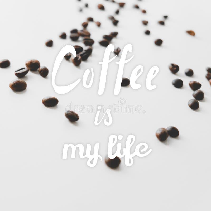 Los granos de café dispersados en la tabla y la mano dibujadas citan el café foto de archivo libre de regalías