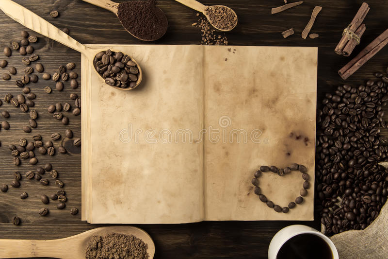 Los granos de café en viejo vintage abren el libro Menú, receta, mofa para arriba Fondo de madera imágenes de archivo libres de regalías