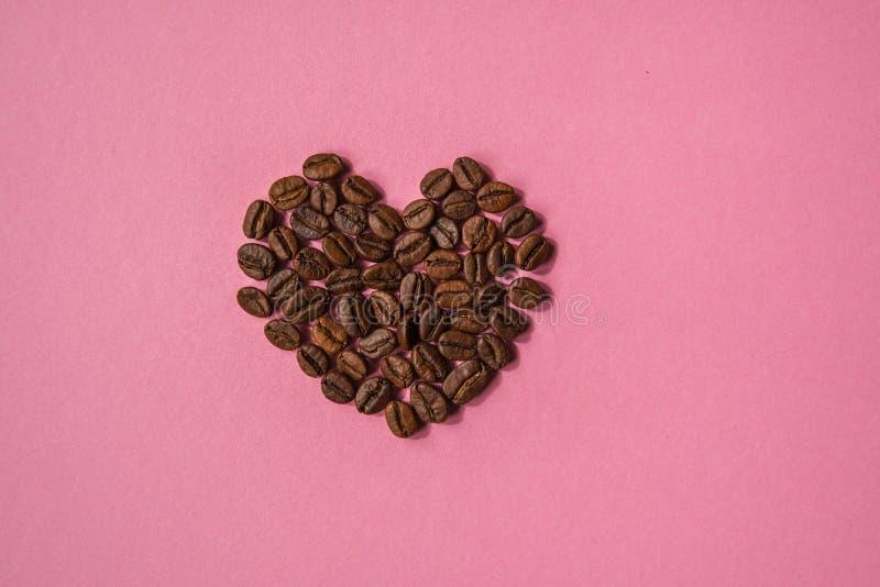 Los granos de café formaron corazones en un fondo rosado Estafa del café del amor foto de archivo