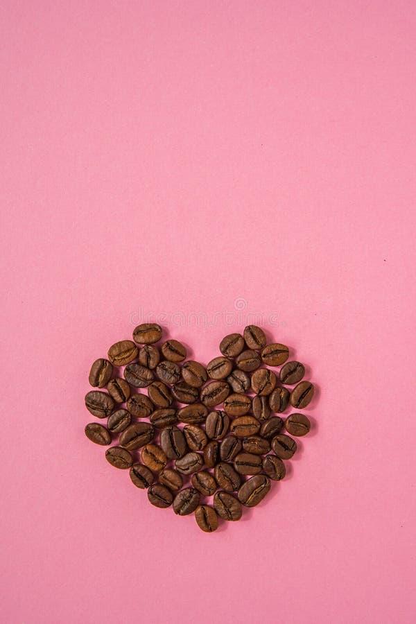 Los granos de café formaron corazones en un fondo rosado Estafa del café del amor imágenes de archivo libres de regalías