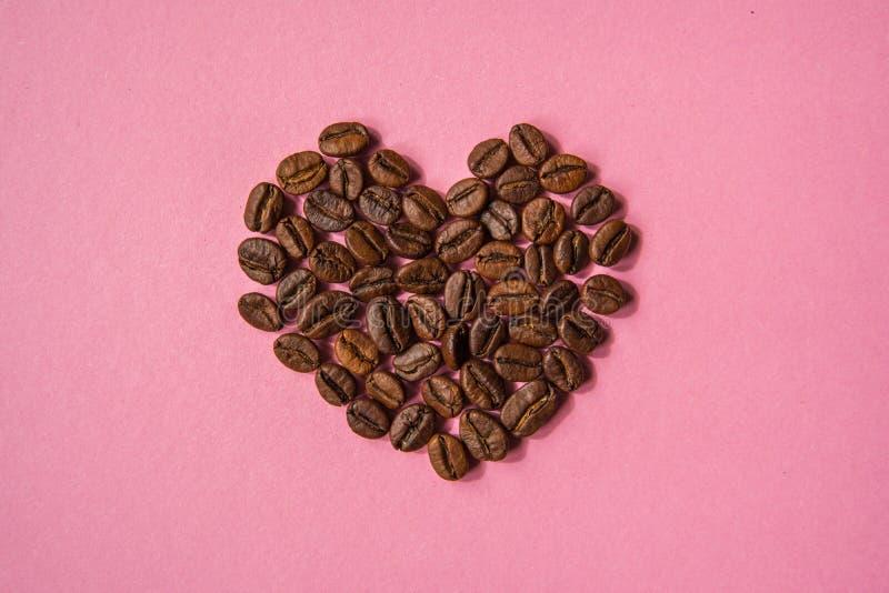 Los granos de café formaron corazones en un fondo rosado Estafa del café del amor fotografía de archivo libre de regalías