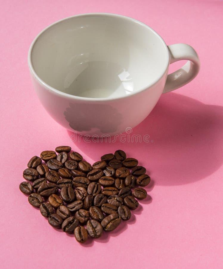 Los granos de café formaron corazones y la taza blanca en un fondo rosado L foto de archivo libre de regalías