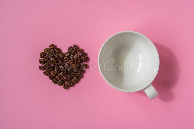Los granos de café formaron corazones y la taza blanca en un fondo rosado L fotografía de archivo