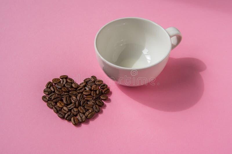Los granos de café formaron corazones y la taza blanca en un fondo rosado L imagenes de archivo