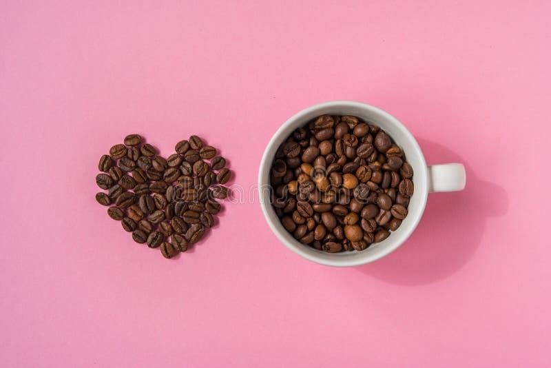Los granos de café formaron corazones y la taza blanca en un fondo rosado L imagen de archivo libre de regalías